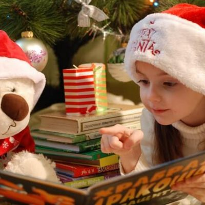 Christmas scene with child reading to a stuffed bear.